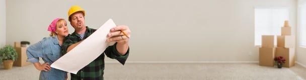 Contratista en casco que discute planes con la mujer en sitio vacío fotografía de archivo libre de regalías