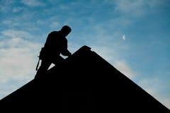 Contratista en la silueta que trabaja en un top del tejado Imagen de archivo libre de regalías