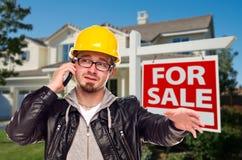 Contratista en sombrero duro delante de la casa y de la muestra Imagen de archivo