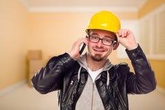 Contratista en sombrero duro en el teléfono celular en casa Fotografía de archivo libre de regalías