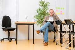 Contratista que habla en Smartphone en oficina moderna fotografía de archivo