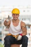 Contratista sonriente que muestra el pulgar para arriba Foto de archivo libre de regalías