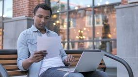 Contrato africano de la lectura del hombre y trabajo en el ordenador portátil, sentándose en banco almacen de video