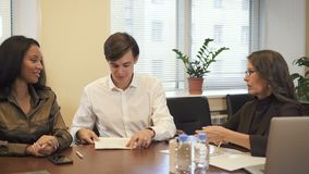 Contrato de assinatura da hipoteca dos pares multi-étnicos no escritório do corretor de imóveis filme