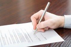 Contrato de assinatura pelo homem de negócios fotografia de stock royalty free