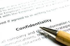 Contrato de confidencialidad con la pluma de madera Fotos de archivo