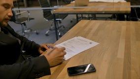 Contrato de empleo de firma del hombre de negocios en oficina durante la reunión almacen de metraje de vídeo