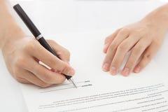 Contrato de firma de la mano femenina. Fotografía de archivo