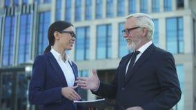 Contrato de firma del hombre de negocios mayor con el consultor femenino joven, apretón de manos metrajes