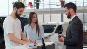 Contrato de firma del vendedor, dando la pluma para servir Individuo joven que pone la firma en el documento Vendedor que da llav metrajes