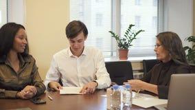 Contrato de firma de la hipoteca de los pares multiétnicos en oficina del agente inmobiliario metrajes