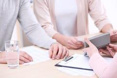 Contrato de firma de los pares jovenes en la agencia del seguro Foto de archivo libre de regalías
