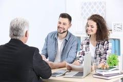 Contrato de firma de los pares jovenes en la agencia del seguro Imágenes de archivo libres de regalías