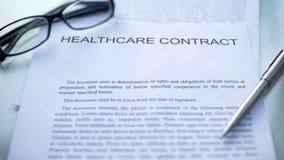 Contrato de la atención sanitaria que miente en la tabla, la pluma y las lentes en el documento oficial fotos de archivo