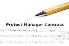 Contrato del gestor de proyecto con la pluma de madera imagen de archivo