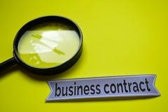 Contrato del negocio con la inspiración del concepto de la lupa en fondo amarillo fotos de archivo libres de regalías