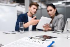 contrato del negocio en el tablero en la oficina con los encargados que miran la tableta borrosa foto de archivo