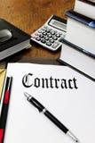 Contrato e calculadora em uma mesa Fotografia de Stock Royalty Free