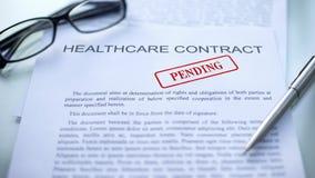 Contrato pendiente, sello de la atención sanitaria sellado en el documento oficial, negocio fotos de archivo libres de regalías