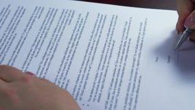 Contratti di firma esecutivi nel suo posto di lavoro - firma falsa stock footage
