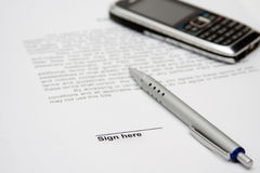 Contratto da firmare e cella Immagine Stock