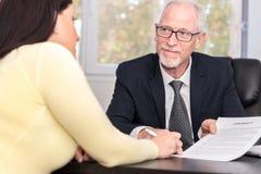 Contratto di firma della donna con il consulente finanziario Fotografia Stock