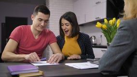 Contratto di firma delle coppie allegre con l'agente immobiliare video d archivio