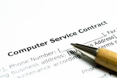 Contratto di servizi del computer con la penna di legno fotografie stock libere da diritti
