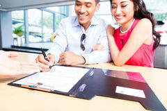 Contratto di vendite di firma delle coppie asiatiche per l'automobile Fotografia Stock Libera da Diritti