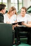 Contratto di vendite di sign delle coppie al commerciante di automobile Fotografia Stock
