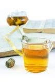 contre des livres mettez en forme de tasse le vert thé ouvert Photo stock