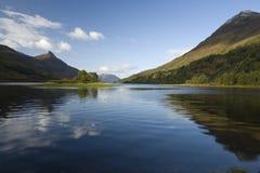 contre la réflexion de montagne d'île sunlit Photographie stock libre de droits