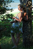 contre le littoral la fille se penche l'arbre Photographie stock
