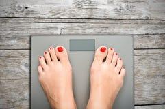 Contribuisca a perdere i chilogrammi con i piedi della donna che fanno un passo su una bilancia Immagini Stock Libere da Diritti