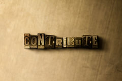 CONTRIBUTE - close-up of grungy vintage typeset word on metal backdrop Stock Images