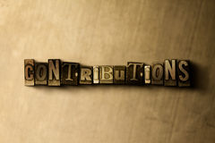 CONTRIBUTIONS - close-up of grungy vintage typeset word on metal backdrop Royalty Free Stock Photography