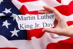 Contro la bandiera americana, la mano che tiene un segno con l'iscrizione Martin Luther King Jr giorno fotografia stock libera da diritti