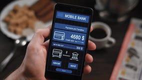 Contro pagamento via l'applicazione mobile di attività bancarie sullo smartphone Un uomo trasferisce i soldi dalla sua carta di c stock footage