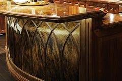 Contro parti superiori del granito e mobilia di legno della cucina. Fotografia Stock