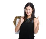 Control asiático de la mujer con el panier y el pulgar para arriba Foto de archivo