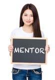 Control asiático de la mujer joven con la pizarra que muestra una palabra del mentor Foto de archivo