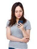 Control asiático de la mujer joven en el teléfono móvil Foto de archivo