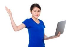 Control asiático del estudiante con el ordenador portátil y la palma abierta de la mano Fotos de archivo