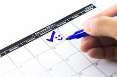 Control azul con sonrisa. Marca en el calendario en el 1 de enero de 2014 Foto de archivo libre de regalías