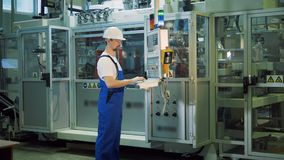 Control board is being operated by a male factory worker. 4K stock video footage