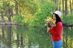Control chino asiático feliz de la sonrisa de la muchacha de la belleza de la mujer que un manojo de paseo de la flor por el lago Imagenes de archivo