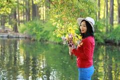Control chino asiático feliz de la sonrisa de la muchacha de la belleza de la mujer que un manojo de paseo de la flor por el lago Imagen de archivo libre de regalías