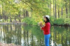 Control chino asiático feliz de la sonrisa de la muchacha de la belleza de la mujer que un manojo de paseo de la flor por el lago Fotografía de archivo libre de regalías