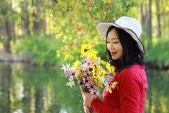 Control chino asiático feliz de la sonrisa de la muchacha de la belleza de la mujer que un manojo de paseo de la flor por el lago Imagen de archivo