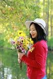 Control chino asiático feliz de la sonrisa de la muchacha de la belleza de la mujer que un manojo de paseo de la flor por el lago Fotos de archivo libres de regalías